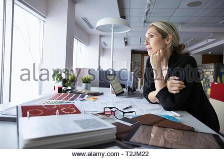 Forward looking female interior designer working in design studio - Stock Image