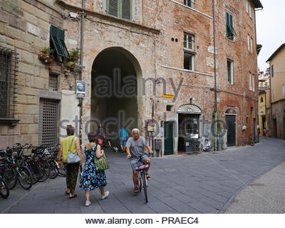 People passing through the entrance arch to the Piazza dell Anfiteatro: Lucca, Italy. - Stock Image