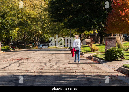 A senior woman walking and exercising herself and her Yorkshire Terrier dog in autumn on a neighborhood street. USA - Stock Image
