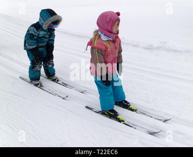 Two little girls (4 yr olds) cross country ski-ing - Stock Image