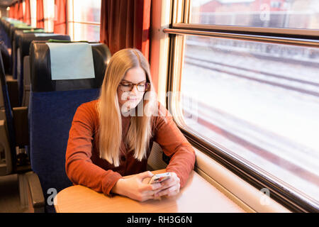 Young woman using cell phone in train - Stock Image