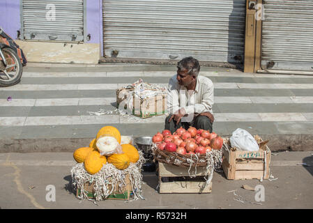 A man selling pumpkins and pomegranates on the street, New Delhi, India - Stock Image