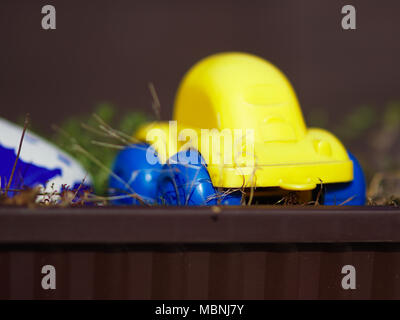 blurred yellow toy car in flower pot - Stock Image