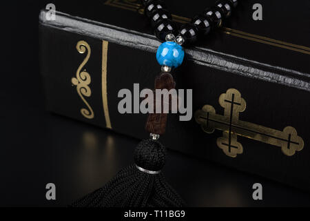 Closeup of Holy Bible and rosary beads with cross on black background. Religion concept and faith. - Stock Image