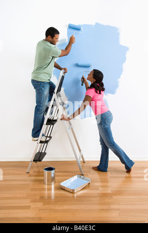 African American male and female couple painting wall blue and smiling at each other - Stock Image