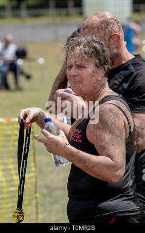 Woman mud runner holds her medal at the finish - Stock Image
