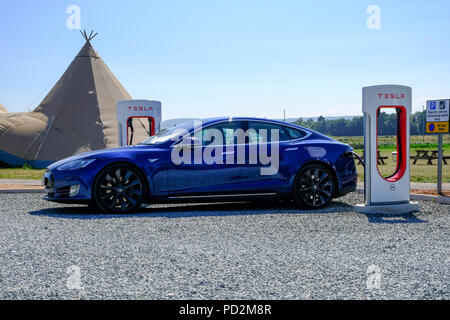 Topsham, Devon, UK. Tesla Model S charging at a Tesla supercharger station in Darts Farm - Stock Image