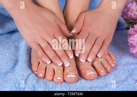 Woman bare feet and hands with french nails polish on blue towel with pink flower in studio. Woman manicure and pedicure concept. Close up - Stock Image