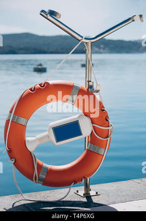 Lifebuoy on the pier or port on the background of the sea on a summer sunny day. - Stock Image