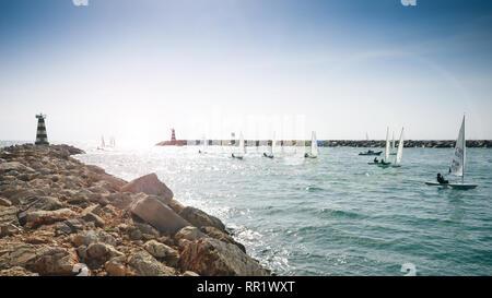 Vilamoura, Portugal - Feb 20, 2019: International sailors in wind sailing boats entering Vilamoura Marina, Portugal - Stock Image