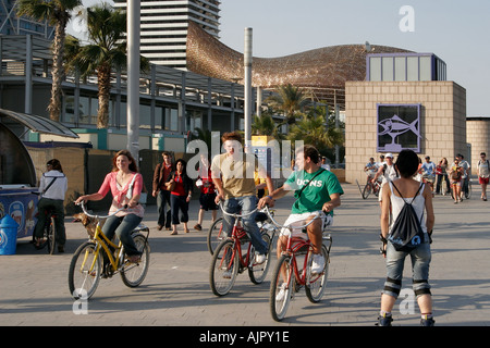 Spain Barcelona beach Platja de la Barceloneta promenade people with bicylces background ffish sculture by Frank Gehry  - Stock Image