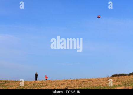 Father and child playing with kite on hillside against blue sky - Stock Image
