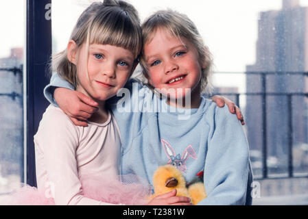 Twin Girls embrace and Smile  for a Photo, 1990, USA - Stock Image