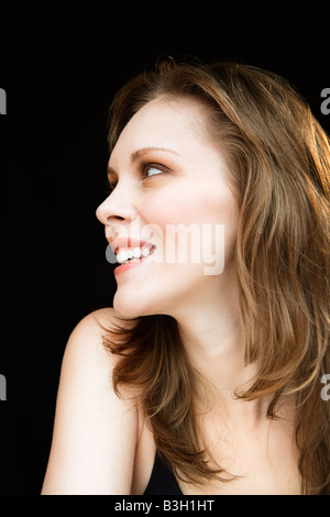 Side view portrait of young adult caucasian female looking off to side - Stock Image