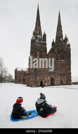 Lichfield Cathedral, Staffordshire, UK. 24th March, 2013. Two young boys enjoying sledging in unseasonal snow in - Stock Image