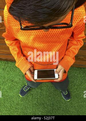 Young boy with black glasses playing with smartphone - Stock Image