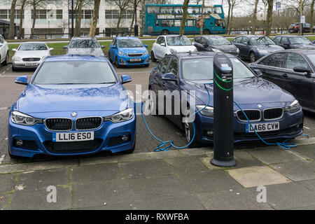Two electric BMW cars being charged in Milton Keynes town centre, Buckinghamshire, UK - Stock Image