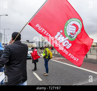 London, UK, 04th April 2019. Minicab drivers block the road on London Bridge protesting against the congestion change on private hire minicabs.  This demonstrators holds and waves the red flag of IWGB (Independent Workers Union of Great Britain). Credit: Graham Prentice/Alamy Live News - Stock Image