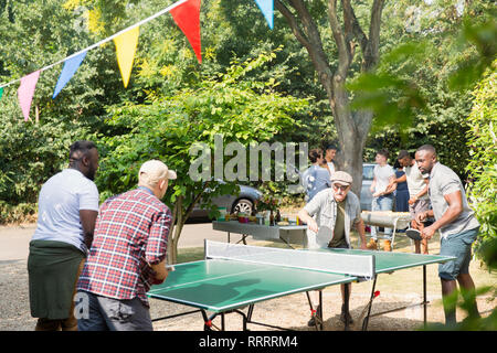 Male friends playing ping pong in sunny back yard - Stock Image