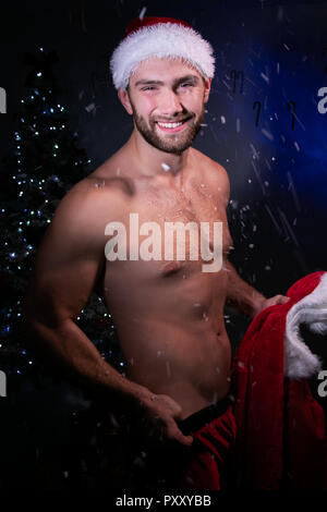 Handsome shirtless male santa holds jacket and smile with christmas tree in background - Stock Image