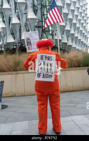 London, UK. 10th December 2018.  A protester dressed in orange jumpsuit with a clown wig in front of the US Embassy in the final 'Shut Guantanamo!' monthly protest of 2018 on the 70th anniversary of the Universal Declaration of Human Rights (UDHR). This declared 'No one shall be subjected to torture or to cruel, inhuman or degrading treatment or punishment' and 'No one shall be subjected to arbitrary arrest, detention or exile.' Guantanamo still has 40 detainees who have been tortured and held in indefinite detention without trial for almost 17 years. Credit: Peter Marshall/Alamy Live News - Stock Image