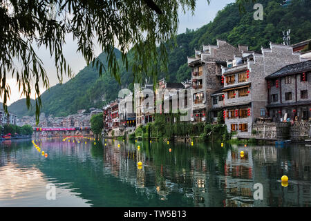 Traditional houses along the Wuyang River with reflection in the water, Zhenyuan, Guizhou Province, China - Stock Image