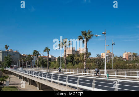 Bridge Puente Pont de Fusta, takes traffic over the Turia Gardens. near former city gate Torres de Seranos (background), Valencia, Spain - Stock Image