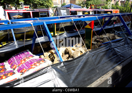 A cargo of coal and wood loaded onto a Traditional working narrowboat, loaded up with coal, smokeless fuel, logs, - Stock Image