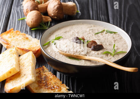 soup puree forest boletus mushrooms close up in a bowl served with toast on the table. horizontal - Stock Image