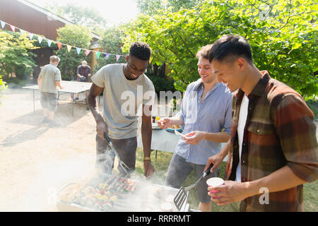 Young men barbecuing in sunny backyard - Stock Image