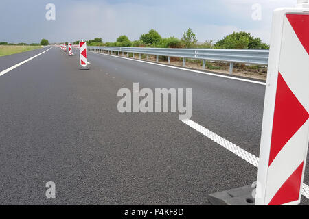 New asphalt lane of a highway divided by a many roadwork marks signs. - Stock Image