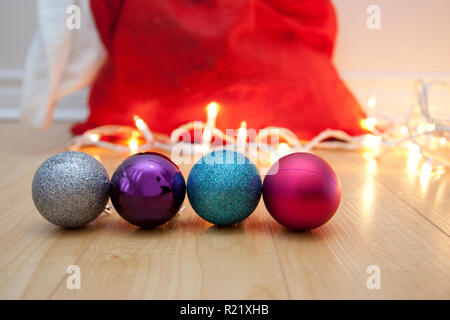 Four sparkly balls or ornaments on the floor with copy space, white lights and a red santa sack - Stock Image
