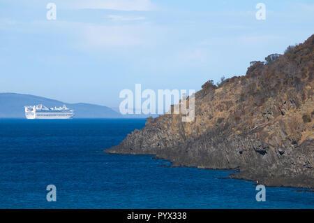 A Princess Cruises ship passes by a rocky headland off the coast of Penneshaw, Kangaroo Island in South Australia, Australia. - Stock Image