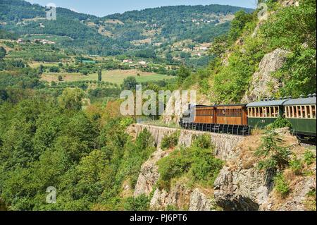 The steam train 'Train de L'Ardeche' descends through the Gorge de Doux on its way back from Lamastre to Tournon sur Rhone, in the Ardeche department - Stock Image