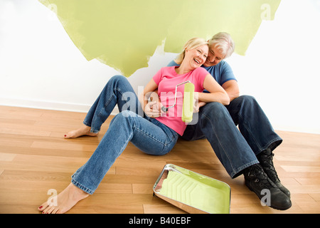 Portrait of happy adult couple sitting in front of half painted wall with paint supplies laughing - Stock Image