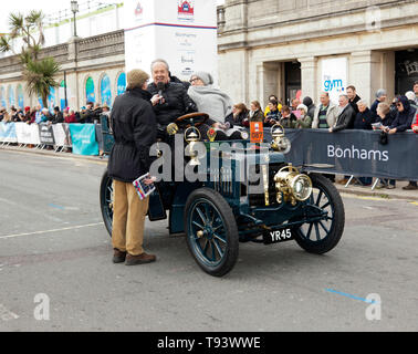 Mr Ian Gwynne being interviewed, after successfully completing the 2018 London to Brighton Veteran Car Run, in a 1901 Panhard Et Levassor. - Stock Image