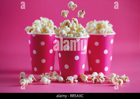 Tasty popcorn falling into cups on pink background. Salty fresh crusty homemade popcorn in pink paper cups. - Stock Image