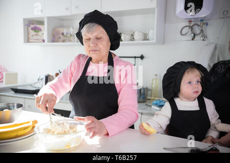 An old woman making pancakes with a little girl in the kitchen. Making dough in the bowl - Stock Image