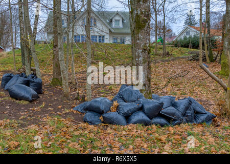 Loads of black bin bags stacked in garden nature - Stock Image