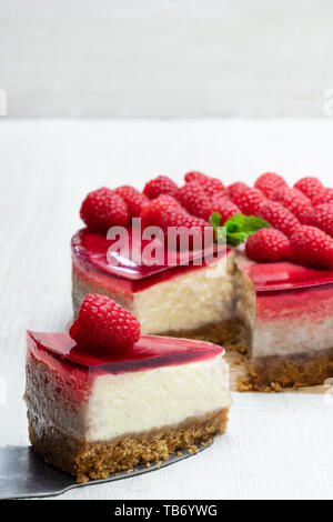 Homemade  cheesecake with raspberry jelly on white wooden table - Stock Image