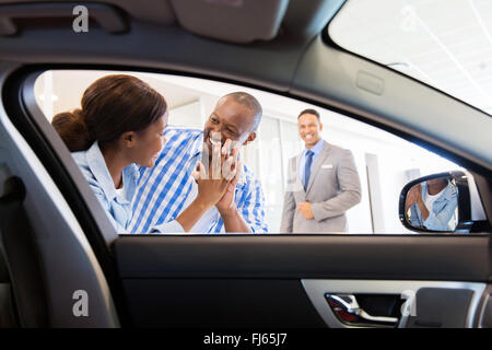 excited African couple at the dealership buying new car - Stock Image