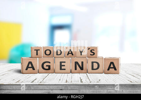 Today's agenda sign on a wooden desk in a bright classroom with colors - Stock Image
