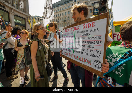 London, UK. 19th April 2019. People protest on Oxford St outside Oxford Circus station as police arrest protesters at Extinction Rebellion's Sea of Protest Police surrounded the yacht shortly after Emma Thompson spoke and put a cordon around Oxford Circus. They began persuading protesters to leave by threatening them with arrest and were cutting off those who were locked on around the bottom of the yacht. There were a number of arrests of protesters who refused to leave. A few tried to get the large crowd to protect the yacht, but XR organisers persuaded them not to physically oppose the polic - Stock Image