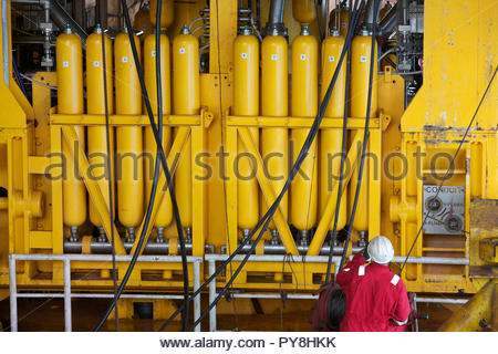 Workers by yellow cylinders on offshore oil platform - Stock Image
