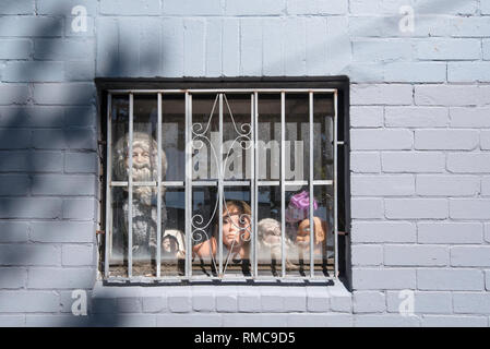 An unusual display of mannequin heads in a window behind steel bars set in a grey painted brick wall - Stock Image