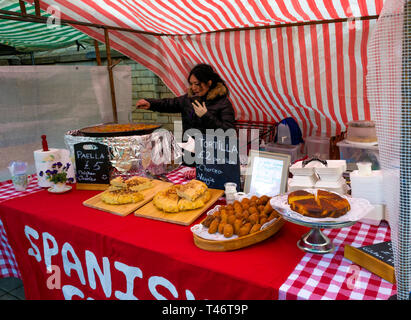 A Spanish woman stall holder at a UK farmer's market displaying food while preparing  steaming hot Paella - Stock Image