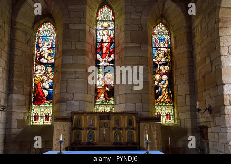 The Parish Church of Saint Mary the Virgin altar with stained glass windows depicting Ascension of Jesus Holy Island of Lindisfarne England UK - Stock Image