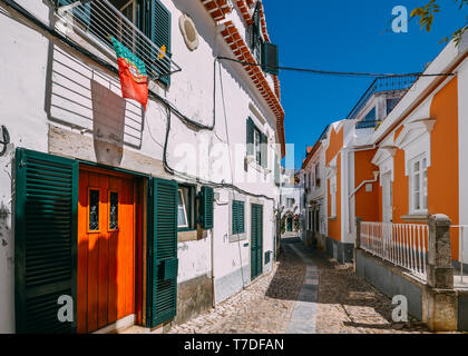 Small narrow cobblestone alley street between whitewashed houses and walls in old town Cascais, Portugal. - Stock Image