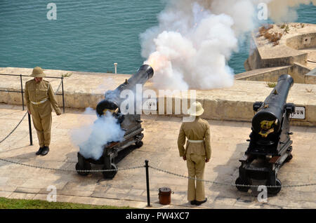 The firing of the noon gun in the Maltese capital of Valletta. The ceremony takes place each day at the saluting battery in the Upper Barracca gardens - Stock Image