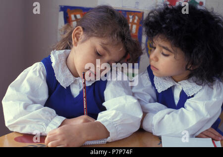 primary school girl hides what she is writing from her peer - Stock Image